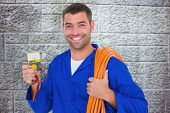 foto of  multimeter  - Smiling electrician with rolled wire and multimeter against grey brick wall - JPG