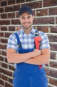 pic of adjustable-spanner  - Confident young male repairman holding adjustable spanner against red brick wall - JPG