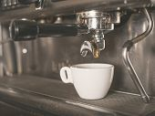stock photo of dispenser  - Professional coffee machine with a small white cup ready for coffee being dispensed - JPG
