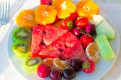 stock photo of watermelon slices  - Strawberries cherries slices of watermelon slices of Mandarin are located on a plate on a white tablecloth table - JPG