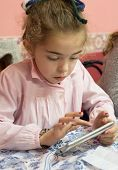 picture of pinafore  - Little girl using an smartphone at school - JPG