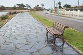 stock photo of rainy day  - Bench in a promenade outdoors in a rainy day - JPG