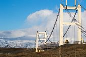 stock photo of suspension  - A modern suspension bridge connects the shore line disrupted by the glacier lagoon in Iceland - JPG
