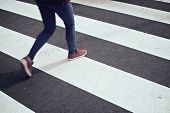 stock photo of pedestrian crossing  - Young woman crossing a zebra crossing - JPG