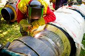 picture of overalls  - Welder working on a pipeline in construction site wearing overall and safety equipment - JPG