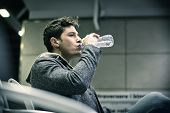 picture of underground water  - Profile shot of handsome young man inside train station drinking water from plastic bottle - JPG