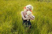 stock photo of tall grass  - Girl hugging a toy bear in a field of tall grass - JPG