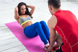 foto of abdominal  - athletic sporty couple friends. Woman doing crunches abdominal exercises on floor in gym with a help of guy concept training exercising workout fitness aerobic. ** Note: Shallow depth of field - JPG