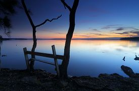 picture of nightfall  - The last colours of sunset aglow on the horizon as nightfall sets in at this peaceful secluded spot on St Georges Basin near Jervis Bay Australia - JPG
