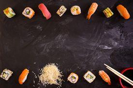 stock photo of soy sauce  - Overhead shot of sushi on dark background - JPG