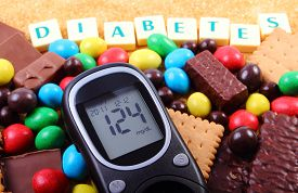 foto of sweet food  - Glucose meter with word diabetes heap of candies cookies and brown cane sugar too many sweets unhealthy food concept of diabetes and reduction of eating sweets - JPG