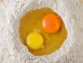 foto of doughy  - Two Light Yellow and Dark Yellow Egg Yolks into Heap of Whole Wheat Flour closeup - JPG