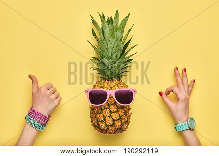poster of Fashion Hipster Pineapple. Female hand OK, YES Gesture Stylish Trendy Watches, Glamor Accessories. Bright Summer Color. Tropical pineapple, Sunglasses. Creative Art concept. Minimal. Summer background