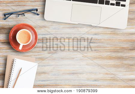 poster of Wood office desk table with laptop computer cup of coffee and glassesflat lay. Top view with copy space (selective focus). Office desk table concept.