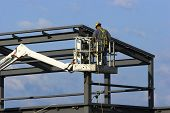 image of cherry-picker  - Construction worker on a cherry picker crane up at the roof of a high building - JPG