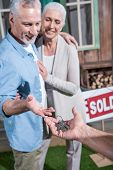 Saleman Giving Keys Of New House To Happy Senior Couple poster