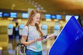 Tourist Girl With Backpack And Carry On Luggage In International Airport, Doing Self Check-in poster
