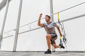 Fitness suspension straps man training legs with suspended lunge exercise at gym. Lower body workout poster