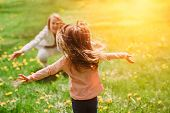 Child running into mothers hands to hug her. Family having fun in the park. Girl is happy to meet h poster
