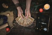 Tarot Cards, Magic Book And Fortune Teller Hands On A Wooden Table Background. Future Reading Concep poster