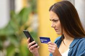 Angry Woman Paying With Credit Card And Smart Phone Outdoors In A Colorful Street poster