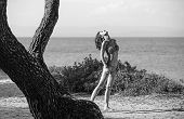 Fashion Model In Swimsuit Sanbathing At Sea Near Tree. Summertime Of Sexy Woman. Happy Woman Relax A poster