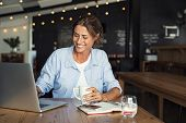 Smiling woman sitting in cafeteria holding coffee mug and working on laptop. Businesswoman checking  poster
