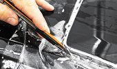 Car Wrapping Specialist Cutting Vinyl Foil Or Film On Car. Protective Film. Applying A Protective Fi poster
