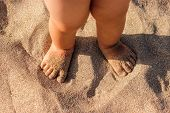 Baby Feet Walking On Sand Beach In The Summer. Close Up. poster