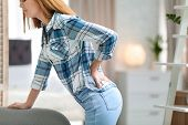 Young Woman Suffering From Back Pain At Home, Closeup poster