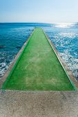 Green Pier Concrete Pier Over Blue Waters, Pier With Green Carpet poster