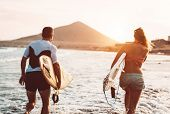 Happy Surfer Couple Running With Surfboards Along The Sea Shore - Sporty People Having Fun Going To  poster