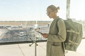 Casually Dressed Female Traveler At Airport Looking At Smart Phone Device In Front Of Airport Gate W poster