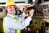 stock photo of electricity meter  - happy male electrician working on industrial machine - JPG
