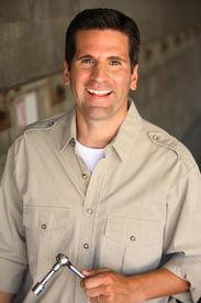 foto of blue-collar-worker  - Smiling Mechanic or Blue Collar Worker in tan shirt - JPG