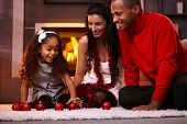 Happy interracial family having fun at home at christmas time, being together, sitting on floor, pla