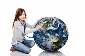 stock photo of auscultation  - Portrait of a little girl auscultate the health of the planet earth with a stethoscope - JPG