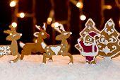Image of christmas setting - gingerbread deers and santa.