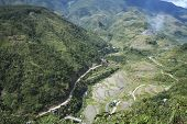 image of ifugao  - road winding through steep valleys of the mountain province of banaue in luzon philippines past flooded traditional rice terraces - JPG