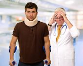 stock photo of cervix  - Young Man Wearing Cervical Collar And Frustrated Doctor Behind It - JPG