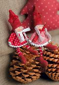 Two christmas rag dolls sitting on fir cones