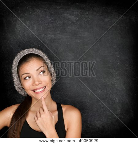 Thinking woman by blackboard. Multiracial hipster university college student pensive and contemplati poster
