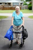 pic of street-walker  - senior woman and walker overloaded with shopping bags in the driveway - JPG