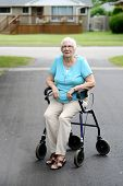 foto of street-walker  - Tired senior woman sitting on walker in the driveway - JPG