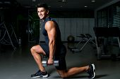 stock photo of dumbbells  - Men Exercising Dumbbell Lunge in the gym