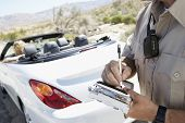 stock photo of policeman  - Closeup of a cropped police officer writing traffic ticket to woman sitting in car - JPG