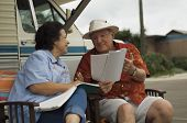 stock photo of palm-reading  - Happy middle aged couple with magazines relaxing outside their motor home - JPG