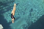 picture of upside  - Active female diver diving upside down into the swimming pool - JPG