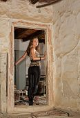 Young woman looking back and entering a derelict house