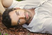 image of hunk  - Portrait of young man outdoors with very handsome face in white casual shirt relaxing outdoors - JPG